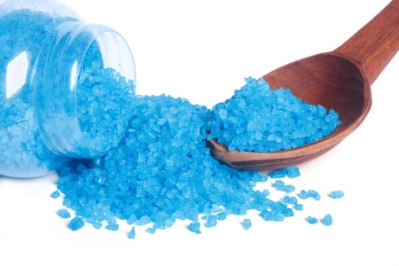 Blue bath salt in a glass jar and a wooden spoon isolated