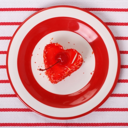 Cake in the form of a red heart with a cherry  top view  photo