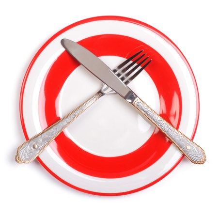 Crossed fork and knife on a plate with a red border  Stock Photo - 18552170