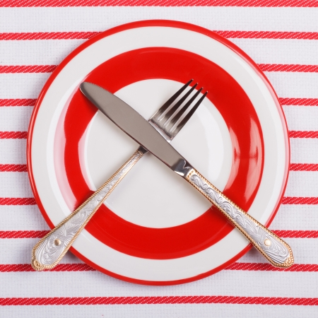 Crossed knife and fork on a red plate on striped tablecloth photo