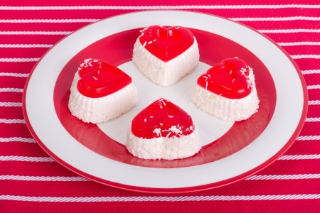 Cakes in the shape of a heart with coconut on a red plate photo