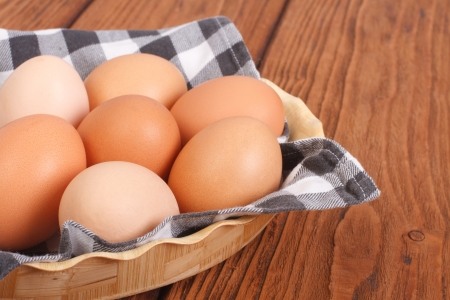 fresh brown chicken eggs in a basket on a napkin on table  photo