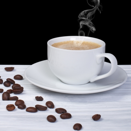 Hot coffee with smoke and coffee beans on wooden table photo