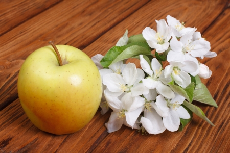 Whole green apple with flowers on wooden table photo