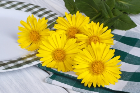 Table setting  Beautiful plate and yellow daisies photo