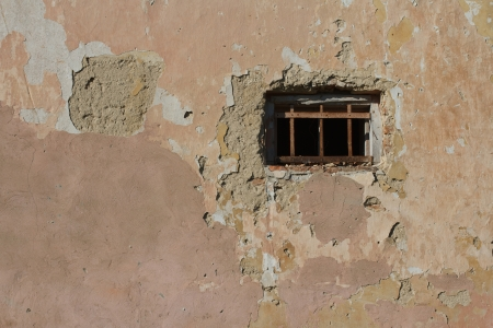 old small window with bars in a wall covered with plaster photo