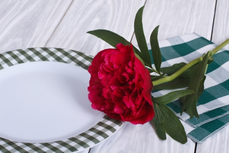 Table setting  Peony and white plate on a wooden table photo