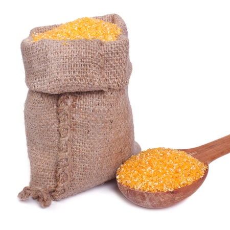 grits: Corn groats in a bag and a wooden spoon isolated on a white