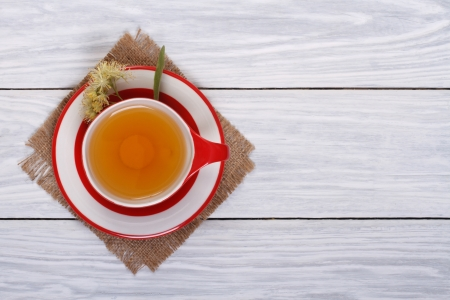 Tea with lime in a red cup on a wooden table  top view photo