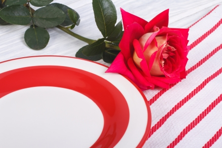 Festive table setting  Flower of red roses and a plate  photo