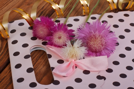 Pink gift bag with bow and cornflowers photo