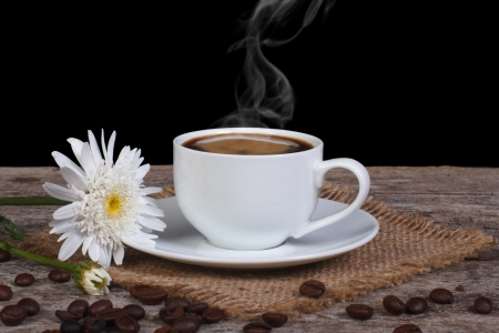 Hot coffee and white chrysanthemum flower on the table photo