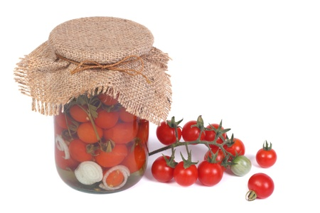 Canned cherry tomatoes in a glass jar and fresh tomatoes photo