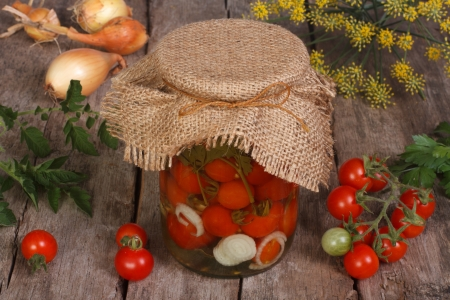 canned cherry tomatoes in a glass jar on wooden table photo