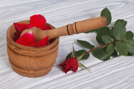 Red petals in a wooden mortar and pestle and a fresh rose bud photo