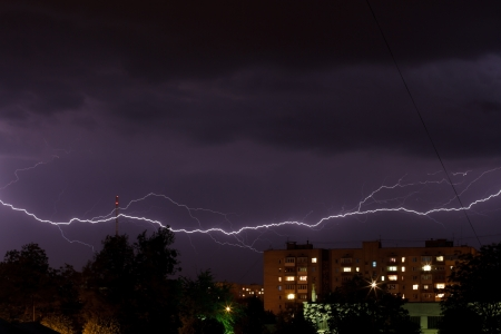 Thunderstorm with lightning in the night sky over the city photo