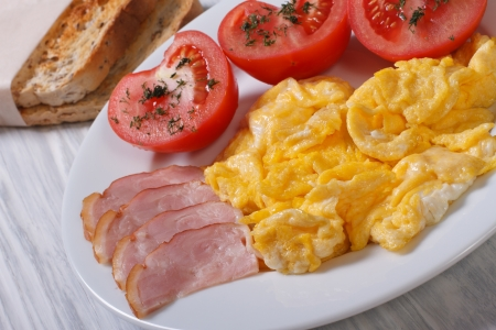 A delicious breakfast  omelet with ham and tomatoes and croutons photo
