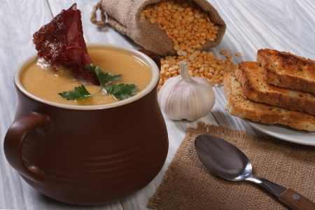 pea soup with smoked ribs in a pot photo