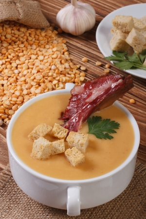 yellow split pea soup with croutons and smoked ribs photo