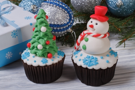 Two muffins Christmas spruce with toys and a snowman photo