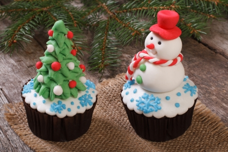 Two Christmas cupcake  Christmas tree and snowman on the table photo