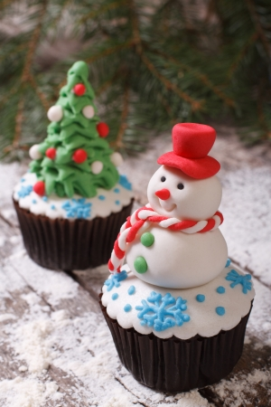 Cupcake Christmas snowman on the background of fir trees photo