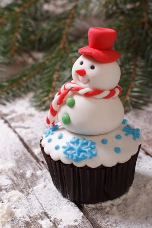 Cupcake Christmas snowman on snow  vertical photo