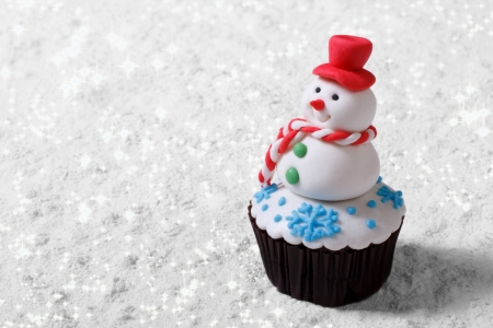 Cupcake Christmas snowman on white snow  horizontal photo