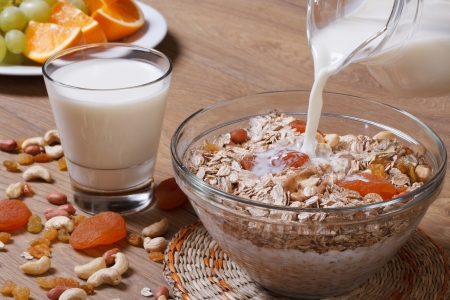 jet milk pouring onto cereal with dried fruits photo