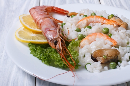 rice with seafood and vegetables in a white plate on the table  photo