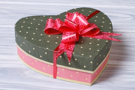 Pink box with green cover in the form of heart with a bow on a wooden table Stock Photo