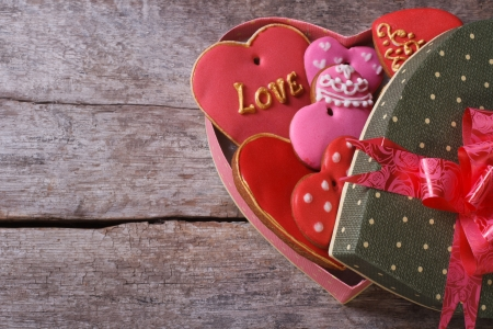 Open gift box with cookies valentines on the old wooden table photo