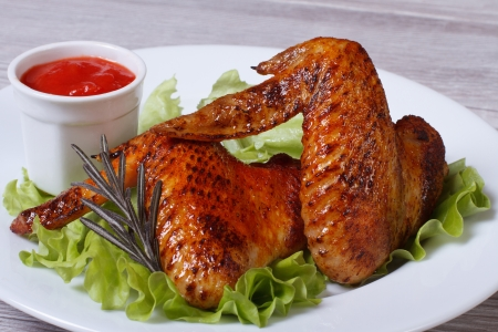 american cuisine: Fried chicken wings with rosemary, lettuce and tomato sauce on the table