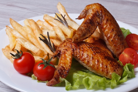 Two fried chicken wings, french fries, tomato and lettuce on a plate  photo