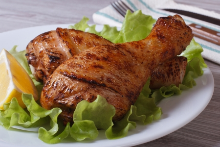 roasted chicken legs with salad and a slice of lemon on a white plate  photo