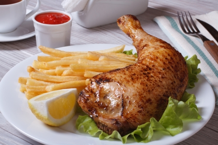 Roasted chicken leg with french fries, lemon and ketchup on a white plate.  photo