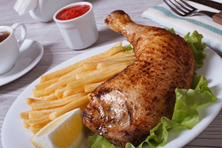 Portion of French fries with chicken leg and lemon on a white plate  photo