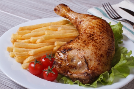 Portion of French fries with chicken leg and cherry tomatoes on a white plate. close-up  photo