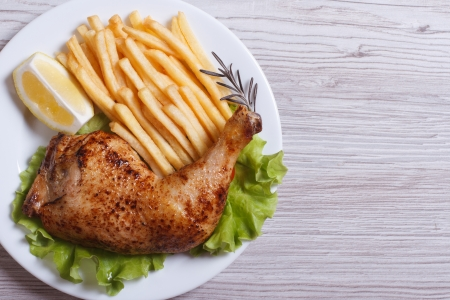 Portion of chicken legs, french fries on a white plate. top view  photo