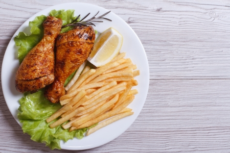 Two fried chicken drumsticks with french fries, rosemary, lemon and lettuce on a white plate. top view
