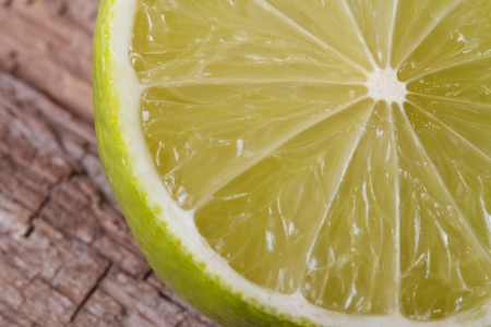 half of fresh juicy lime on background wooden table closeup photo