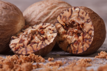 sliced and grated nutmeg on an old wooden table  macro Stock Photo
