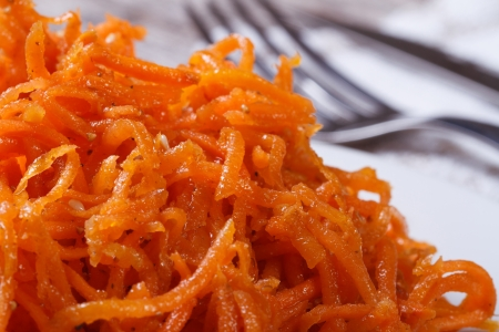 grated carrots with spices on white plate closeup  photo