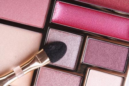 eyeshadow in pink tones and lip gloss and applicator close-up. macro