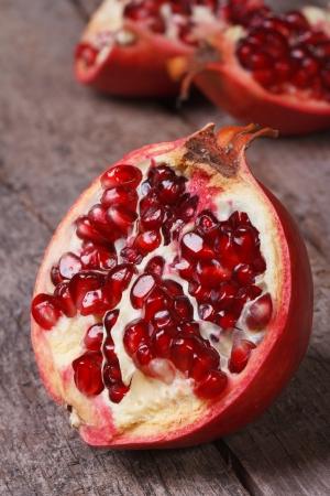 half cut: cut ripe pomegranate on an old wooden table vertical. closeup. macro