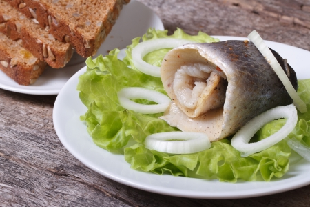 pickled herring roll with onion rings on lettuce leaves close up on the table and homemade bread on a plate.  photo