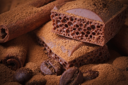aerated: aerated chocolate, coffee beans and cinnamon sticks closeup. Background. macro  Stock Photo