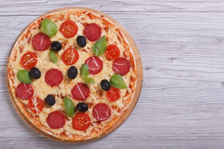 whole pizza with salami, tomato, cheese, olives and basil on the table. top view  photo