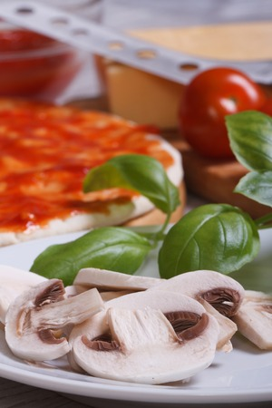 preparation of ingredients for pizza: sliced mushrooms, basil, dough, tomato. Vertical  photo