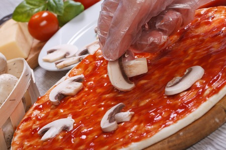 pizza base: Hand chef puts on a pizza base champignons mushrooms.
